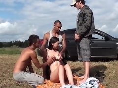 Sexy girls is getting gang banged by several men out in the grass