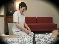 Beautiful Asian masseuse strokes a man's hard cock through