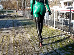 domina in green latex and dark-hued shoes